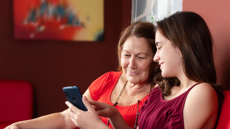 SmartBimodalHearingSolution-GrandmaGranddaughterCellPhone_es.png
